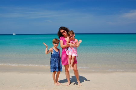 Family beach vacation. Happy mother with kids having fun near sea. Summer vacation with children  photo