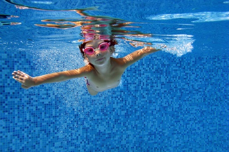 Happy child swims underwater in swimming pool  Kids sport Stock Photo
