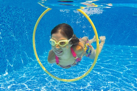 Happy child swims underwater in swimming pool  Smiling active girl in pool  Kids sport photo
