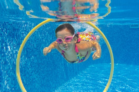 Happy child swims underwater in swimming pool  Smiling active girl in pool  Kids sport Reklamní fotografie
