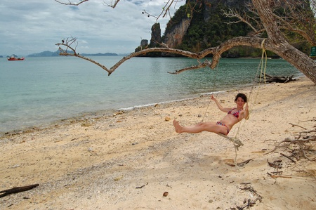 Woman swinging on the tropical beach photo