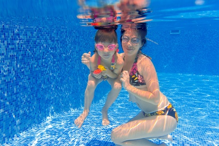 Underwater smiling family having fun and playing in swimming pool. Happy mother and kid swim underwater. Summer vacation.