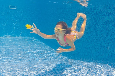 Happy healthy child swims underwater in swimming pool. Smiling active girl in pool playing with fish. Kids sport and fun photo