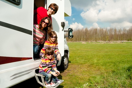 Family vacation in camping  Happy active parents with kids travel on camper  Family having fun near their motorhome  Spring vacation trip with children