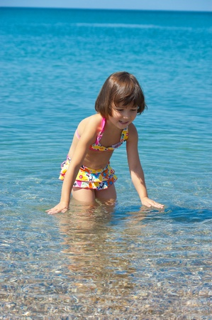 Family summer beach vacation  Happy active child splashing and playing in sea  Little healthy girl having fun on beautiful beach  Vertical image photo