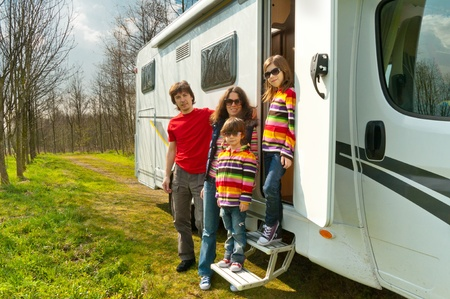Family vacation in camping  Happy active parents with kids travel on camper  RV   Family having fun near their motorhome  Spring vacation trip with children Stock Photo - 13510131