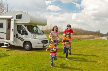 Family vacation in camping  Happy active parents with kids travel on camper  RV   Family having fun near their motorhome  Spring vacation trip with children
