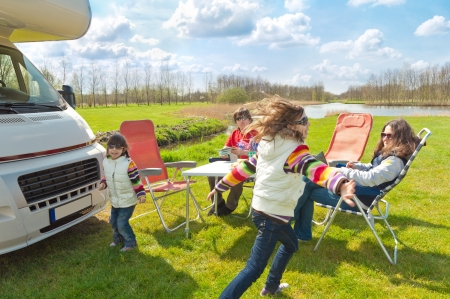 Family vacation in camping  Happy active parents with kids travel on camper  RV   Family having fun near their motorhome  Spring vacation trip with children Stock Photo - 13697331