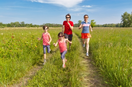 Family sport, jogging outdoors. Happy active parents with kids run. Healthy family lifestyle concept photo