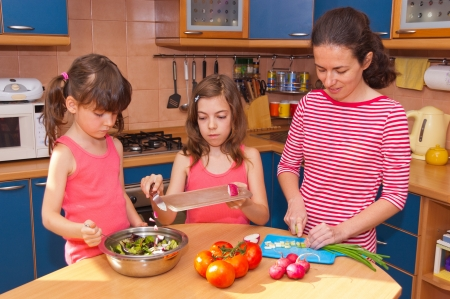 Family cooking at home  Happy smiling mother with kids cook healthy food together at kitchen  Family preparing salad