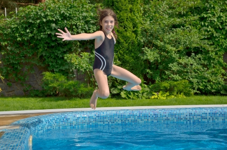 Happy active child jumps to swimming pool  Beautiful smiling girl having fun on summer vacation  Kids sport and holiday Stock Photo