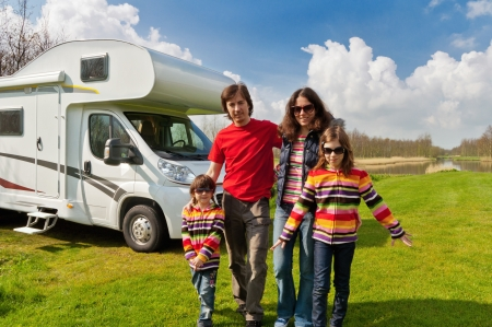 Family vacation in camping, camper trip  Happy active parents with kids travel on RV  Family having fun near their motorhome  Spring vacation trip with children  Stock Photo