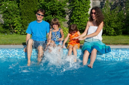 Family summer vacation  Happy parents with two kids having fun and splashing near swimming pool  Vacation with children photo