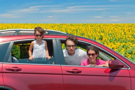 Family summer vacation, travel by car Happy active parents with child having fun in car trip, looking at beautiful nature