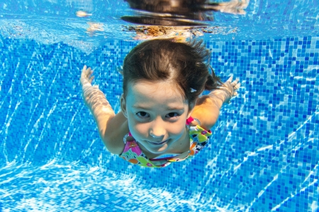 Happy smiling underwater child in swimming pool, beautiful girl swims and having fun  Kids sport on family summer vacation  Active holiday photo