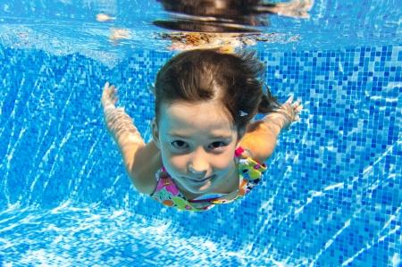 Usměvavé podvodní dítě v bazénu, krásné dívky plave a baví děti Sport na Rodinné prázdniny Aktivní dovolená