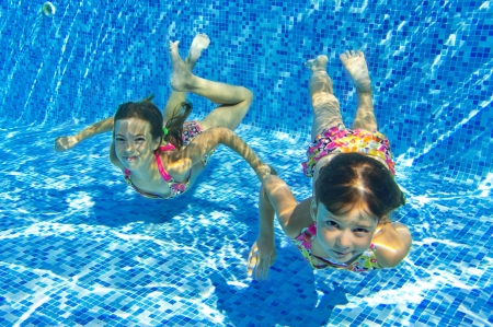 Happy smiling underwater children in swimming pool, beautiful girls swim and having fun  Kids sport on family summer vacation  Active holiday