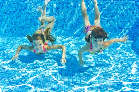 Happy smiling underwater children in swimming pool, beautiful girls swim and having fun  Kids sport on family summer vacation  Active holiday photo