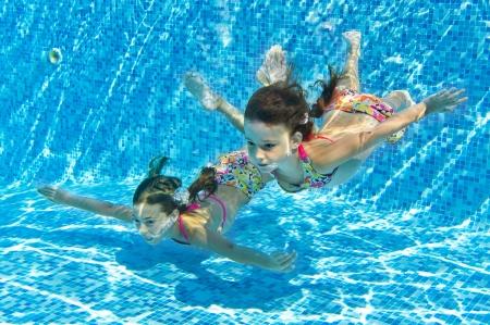 girl underwater: Gelukkige het glimlachen onderwater kinderen in zwembad, mooie meisjes zwemmen en plezier maken Kids sport op familie zomervakantie Actieve vakantie