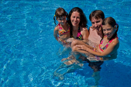 pool fun: Happy family with two kids in swimming pool  Smiling parents and children on summer vacation swim and having fun  Family sport, active healthy holiday