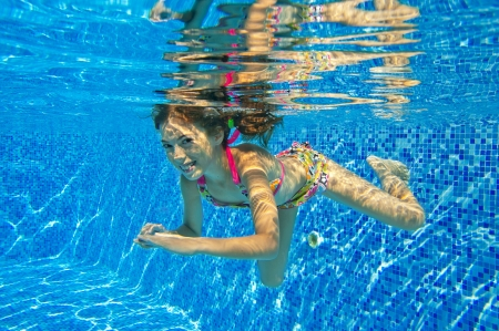 Happy smiling underwater child in swimming pool, beautiful girl swims and having fun Kids sport on family summer vacation Active holiday