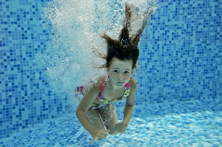 Happy smiling underwater child jumps to swimming pool, beautiful little girl swims and having fun  Kids sport on family summer vacation  Active holiday photo