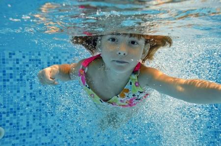 幸せな笑みを浮かべて水中子供にジャンプ スイミング プール、美しい小さな女の子を泳ぐし、家族休暇アクティブな夏休みキッズ スポーツを楽し