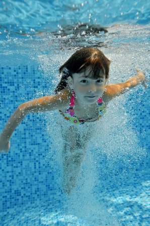 Happy smiling underwater child jumps to swimming pool, beautiful little girl swims and having fun  Kids sport on family summer vacation  Active holiday Stock Photo