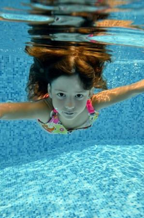 girl underwater: Happy lachende kind onder water springt naar een zwembad, een prachtig klein meisje zwemt en plezier Kids sport op familie zomervakantie Actieve vakantie