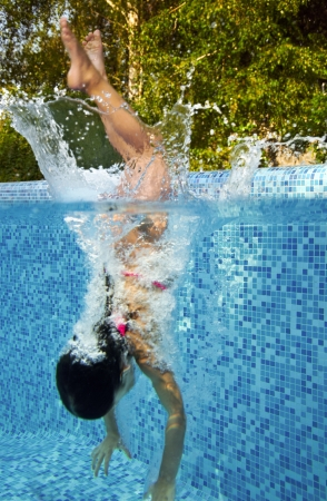Active underwater child jumps to swimming pool, little girl swims and having fun  Kids sport on family summer vacation  Active holiday