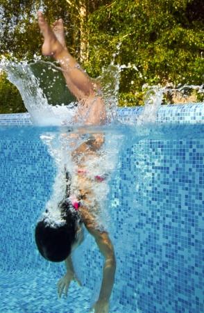 Aktivní podvodní dítě skočí do bazénu, holčičko plave a baví děti sportu na rodinné letní dovolenou Aktivní dovolenou