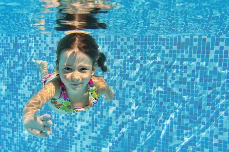 Happy smiling underwater child in swimming pool, beautiful girl swims and having fun  Kids sport on family summer vacation  Active healthy holiday photo
