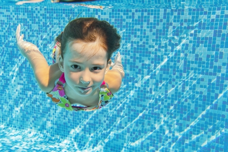 Happy smiling underwater child in swimming pool, beautiful girl swims and having fun  Kids sport on family summer vacation  Active healthy holiday