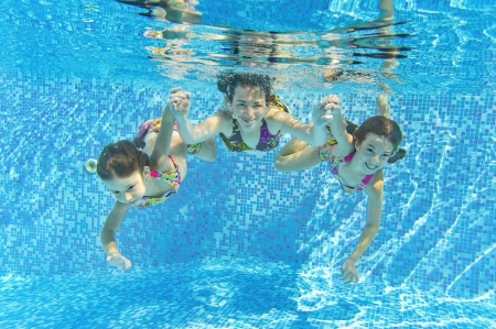 Happy smiling family underwater in swimming pool  Mother and children swim and having fun  Kids sport on family summer vacation  Active healthy holiday