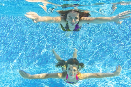 Happy smiling family underwater in swimming pool  Mother and child swim and having fun  Kids sport on family summer vacation  Active healthy holiday Stock Photo
