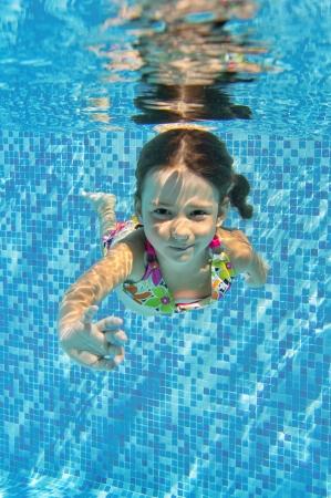 girl underwater: Gelukkig glimlachend onderwater kind in zwembad, mooi gezond meisje zwemt en plezier Kids sport op familie zomervakantie Actieve vakantie Verticale beeld Stockfoto