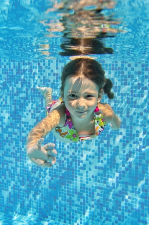 Happy smiling underwater child in swimming pool, beautiful healthy girl swims and having fun  Kids sport on family summer vacation  Active holiday  Vertical image