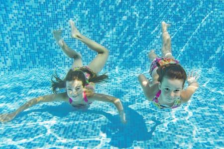 natacion: Feliz ni�os sonrientes bajo el agua en piscina, hermosas ni�as sanas nadar y divertirse el deporte para ni�os en vacaciones vacaciones familiares de verano activo Foto de archivo