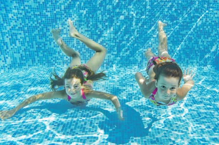 Happy smiling underwater children in swimming pool, beautiful healthy girls swim and having fun  Kids sport on family summer vacation  Active holiday