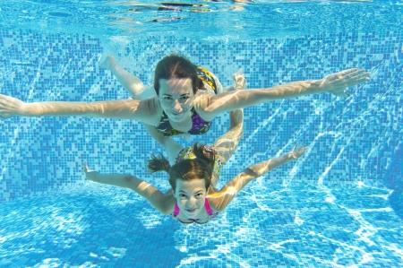 girl underwater: Happy lachende gezin onderwater in het zwembad voor moeder en kind zwemmen en plezier maken Kids sport op familie zomervakantie Actieve gezonde vakantie Stockfoto