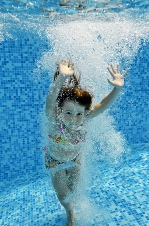 Glücklich lächelnde Unterwasser Kind springt zum Swimmingpool, schöne kleine Mädchen schwimmt und Spaß Kids Sport auf Sommerurlaub mit der Familie Aktivurlaub Standard-Bild
