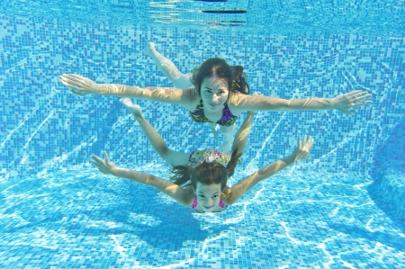 Happy smiling family underwater in swimming pool  Mother and child swim and having fun in water  Kids sport and fitness on family summer vacation  Active healthy holiday