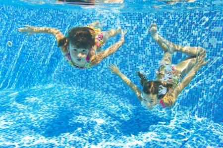 niños nadando: Feliz niños sonrientes bajo el agua en piscina, hermosas niñas sanas nadar y divertirse en el agua deporte Niños en vacaciones vacaciones familiares de verano activo