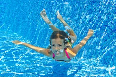 nadar: Feliz ni�o sonriente bajo el agua en piscina, hermosas nada ni�a sana y divertirse en el agua deporte Ni�os en vacaciones vacaciones familiares de verano activo