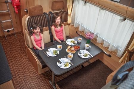 家族での休暇、RV 休日旅行、キャンプの幸せなキャンピングカーの子供に子供旅行の笑みを浮かべてモーター ホーム インテリアで食べる 写真素材