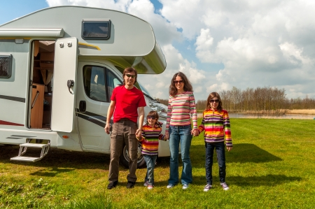 Family vacation in camping, holiday trip in camper  Happy active parents with kids travel on RV  Family having fun near their motorhome  Spring vacation trip with children