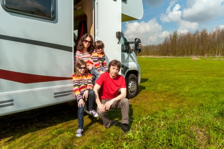 Family vacation in camping, holiday trip in camper  Happy active parents with kids travel on RV  Family having fun near their motorhome  Spring vacation trip with children photo