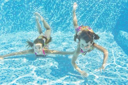 Felices ni�os sonrientes bajo el agua en piscina photo