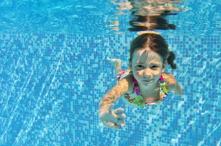 Happy smiling underwater child in swimming pool  photo