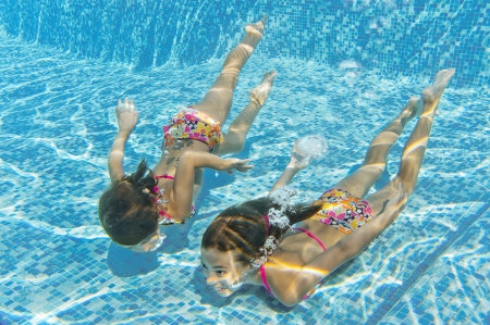 Happy smiling underwater children in swimming pool  photo